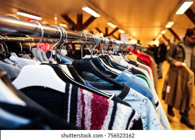 Sweaters on hangers in a thrift shop in Sweden, out of focus shoppers in the background.