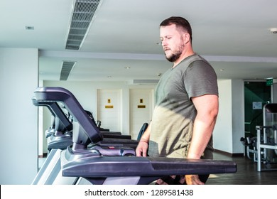Sweating chubby man walking on running track, warming up on gym treadmill