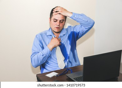 Sweating office worker. Wet shirt. Bad work conditions. Unhappy manager. Summer heat. No air conditioning in the building.