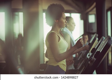 Sweating it out on the treadmill. Women at gym.
