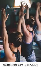 Sweating people practicing yoga during retreat in studio