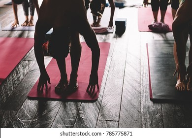 Sweating people practicing yoga during retreat in studio