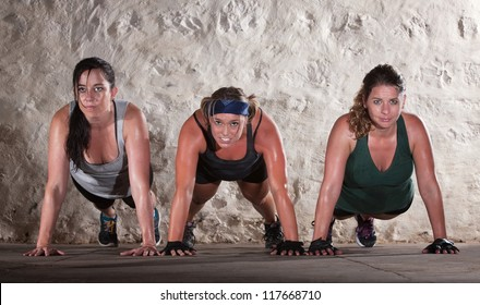 Sweating women doing push ups during bootcamp workout