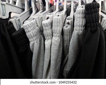 Sweatpants or track pants or sportswear hanging on the rack at clothing department