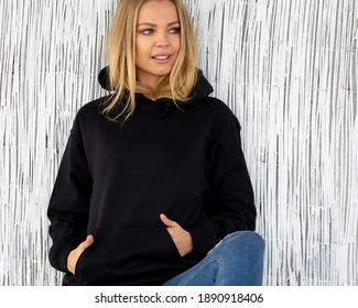Sweatshirt hoodie mockup. A nice smiling blonde poses in a black sweatshirt against a white wall. She is sitting facing the camera.