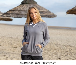 Sweatshirt template. Smiling blond woman wears grey hoodie on beach in summer or autumn. She stands in front of camera with hands in pockets. Copy space on cloth for mockup.