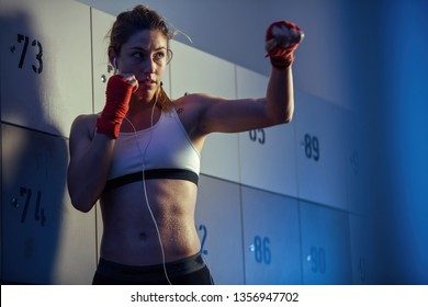 Sweaty athletic woman in fighting stance preparing for boxing training while listening music on earphone in gym's dressing room.