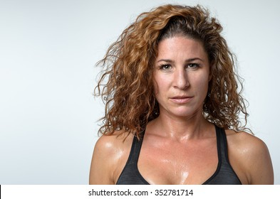 Sweaty attractive young woman with a sheen of perspiration on her skin and lovely curly hair looking directly at the camera with a serious expression, head and shoulders on grey