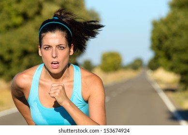 Sweaty female athlete running on rural road. Hispanic woman training sprint and exercising hard for intense marathon.