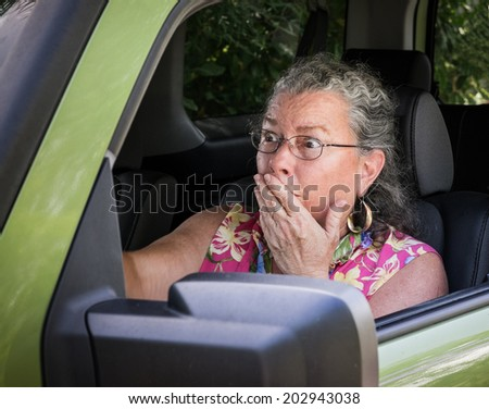 Sweaty Hot Senior Woman Driver Looking Terrified Holding Hand To Mouth In Drivers Seat