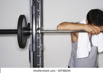 Sweaty man resting on barbell after workout