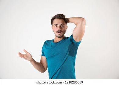 Sweaty man with stain on t-shirt against white background. Using deodorant