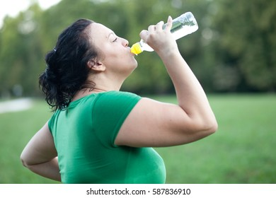 Sweaty overweight plus sized woman drinking water after workout
