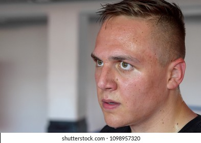 Sweaty red-faced young man after a workout dripping perspiration looking into the camera in a close up head shot