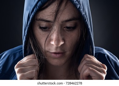 Sweaty Woman with Blue Raincoat Holding a Hood