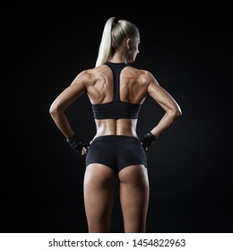 Sweaty woman having a break in a gym showing her well trained body back muscles. Rear view of fitness female with muscular body. Muscular back and buttocks. Energy fitness motivation.