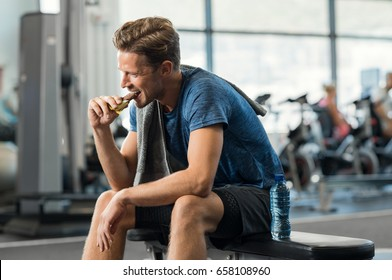 Sweaty young man eating energy bar at gym. Handsome mid guy enjoying chocolate after a heavy workout in fitness studio. Fit man biting a snack and resting on bench. - Shutterstock ID 658108960