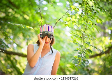 Sweden - 07/08/2013: A young woman in a green forest looking through binoculars