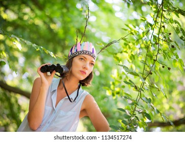 Sweden - 07/08/2013: A young woman in a green forest holding binoculars