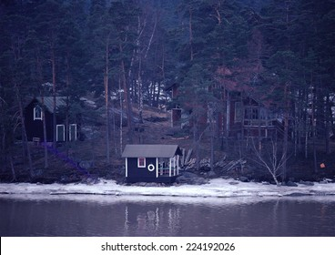 Sweden, cabins in woods near water's edge