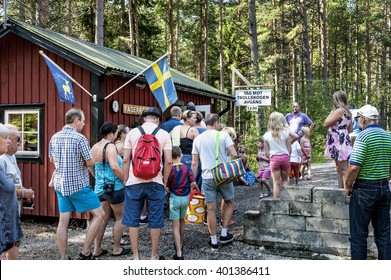 Sweden, Fagerror: People tourists tourists men women kids at rural train station buy tickets and wait for the arrival of an old traditional vintage diesel engine locomotive. August 08, 2014