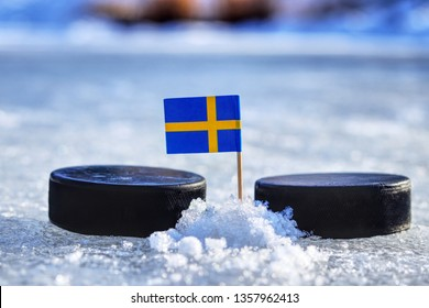 Sweden flag on toothpick between two hockey pucks. Winter classic. Flag on frozen pond on unkempt ice. Traditional pucks for international matches