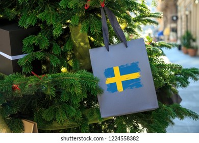 Sweden flag printed on a Christmas shopping bag. Close up of a gift bag as a decoration on a Xmas tree on a street. New Year or Christmas shopping, local market sale and deals concept.