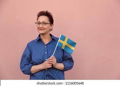 Sweden flag. Woman holding Swedish flag. Nice portrait of middle aged lady 40 50 years old with a national flag over pink wall background.Learn Swedish language. Visit Sweden concept.