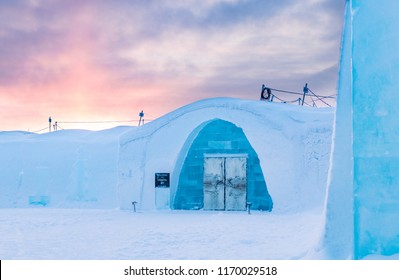 Jukkasjärvi / Sweden - January 16 2018: The first sun rays of the year rising over the original Ice Hotel in northern Sweden. Magical light with the entrance to the igloo hotel.
