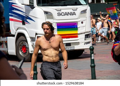 Malmö, Sweden - July 20, 2019: A bare chested man is walking in front of a Scania truck as they both participate in the annual gay pride parade in Malmö, Sweden.