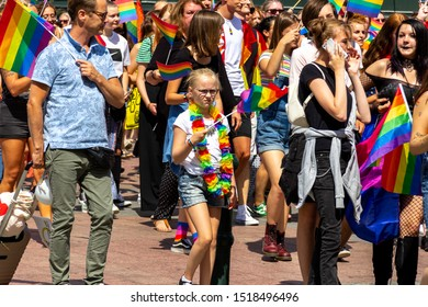Malmö, Sweden - July 20 2019: A young girl in glasses with a sceptical look waves her rainbow colored pride flag while attending the 2019 pride parade through the streets of downtown Malmö, Sweden.