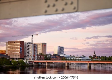 Umeå, Sweden - Jun 18, 2021: Umeå city skyline seen from the old bridge (gamla bron in Swedish) over Ume river during sunset.