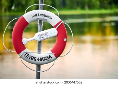 Umeå, Sweden - Jun 18, 2021: Lifebuoy with text Umeå kommun (Umeå municipality in english) with the Ume River in background.