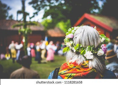 Örebro, Sweden – Juni 22 2018: Celebration of Midsommar (midsummer) in Wadköping. Grey haired woman  with flower wreath from the back, and people dancing around the maypole in the blurred background.