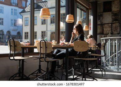 VÄSTERVIK, SWEDEN - MARCH 19 2020: Italian girl with black sweater sits in front of the window in the sun in a cafe and is calling someone with her smartphone in  Västervik (Vastervik) in Sweden