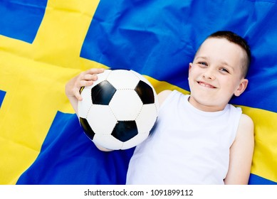 Sweden national football team. Child boy with football ball and Swedish flag