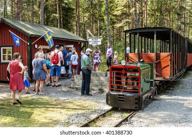 Sweden, Oland, Fagerror: People tourists tourists men women kids at rural train station buy tickets and wait for a ride with an old German vintage diesel engine locomotive. August 08, 2014
