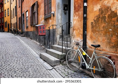 Sweden quaint cobblestone street in picturesque Gamla Stan, Stockholm's oldest neighborhood. Parked bicycles lean against the colorful plaster buildings. Biking is a popular way to get around town.