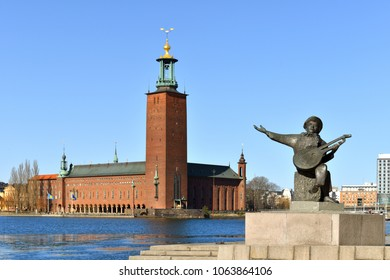 SWEDEN, STOCKHOLM - MARCH 27, 2018: Evert Taube monument on background of Stockholm City Hall (1923), building of Municipal Council for City of Stockholm in Sweden