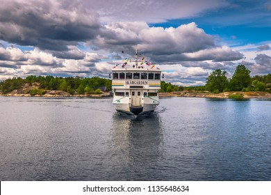 Swedish Archipelago - June 23, 2018: A ferry boat approaching a small dock in the Swedish Archipelago during Midsummer, Sweden