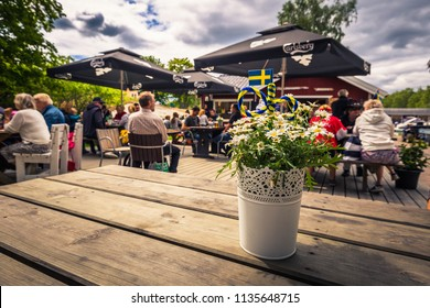 Swedish Archipelago - June 23, 2018: Vase in a table in a Midsummer gathering in the island of Moja in the Swedish Archipelago during Midsummer, Sweden