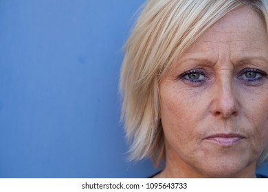 Swedish, blond, middle-aged woman pondering over something.
