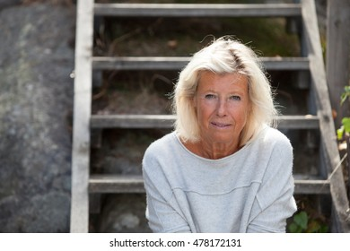 Swedish, caucasian, older woman looking into the camera while thinking about something.
