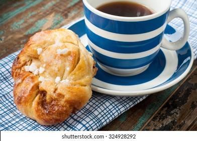 Der schwedische Zimtbeerbun wird auf einem rustikalen Holztisch mit einer Tasse frisch gebrühtem Kaffee in einer blau-weiß gestreiften Tasse und Untertasse serviert. Kaffee und ein Knospen ist eine Tradition in Schweden, bekannt als fika.