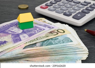Swedish currency, calculator, toy house and pen to represent property finance.