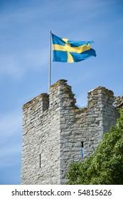 Swedish flag above medieval wall on Gotland