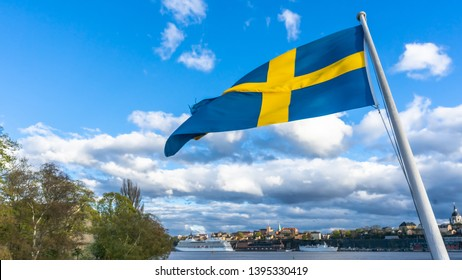Swedish flag against blue sky with white clouds. Beautiful swedish flag seen in Stockholm. Swedish flag fluttering in wind on the ship. Sveriges nationaldag. National Day of Sweden. Swedish Flag Day.