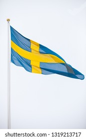 The Swedish flag against a white, overcast sky.