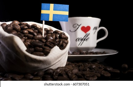 Swedish flag in a bag with coffee beans isolated on black background