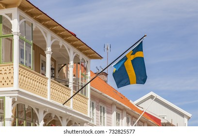 Swedish flag flying on a street with traditional wooden houses Marstrand, Sweden.